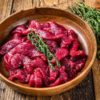 Raw uncooked beef meat sliced in strips with fresh herbs for beef stroganoff. wooden background. Top view
